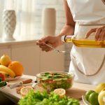 tipuri de ulei, femeie toarna ulei in salata