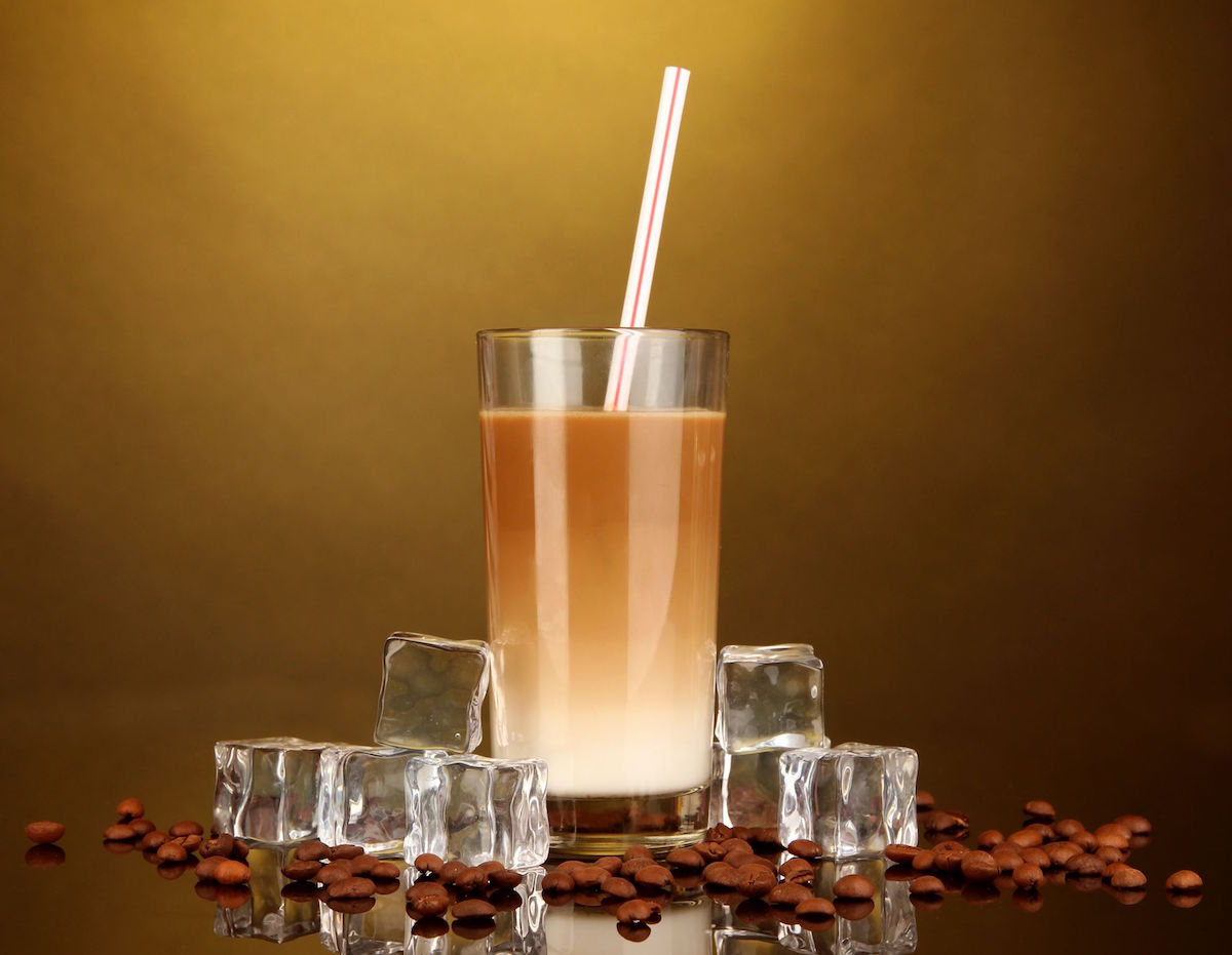 18573406 – cold coffee with ice in glass on color background