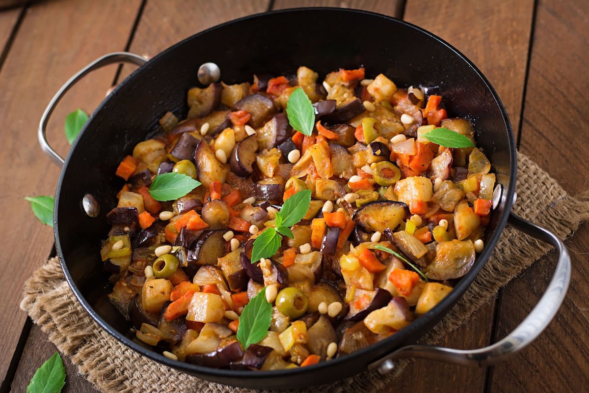 48125736 – italian caponata with frying pan on a wooden background